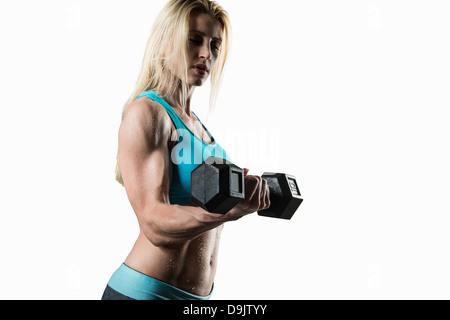 Jeune femme effectuant des biceps, studio shot Banque D'Images