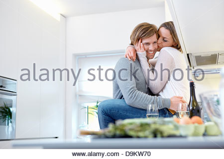 Couple hugging in kitchen, woman sitting on sofa Banque D'Images