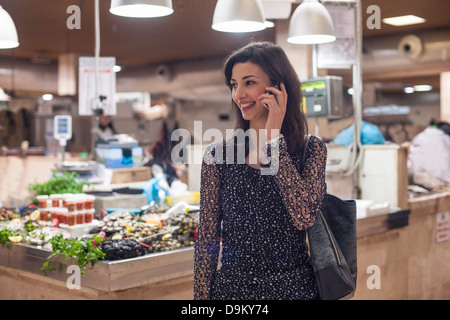 Woman on cell phone in fish market Banque D'Images