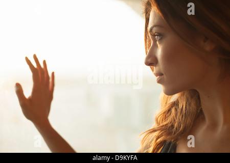 Jeune femme à la fenêtre de Banque D'Images