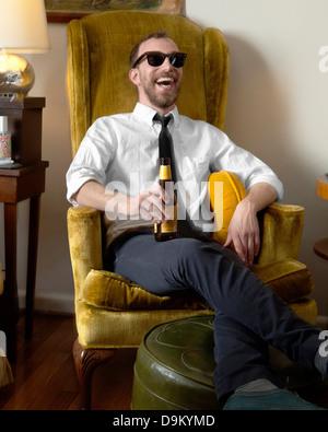 Jeune homme en fauteuil de détente et de rire Banque D'Images