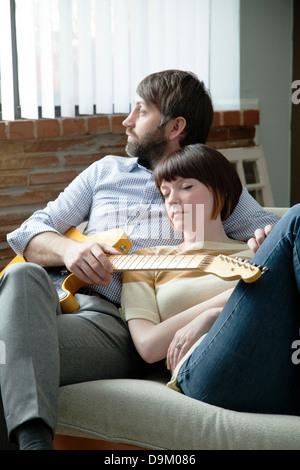 Jeune femme dormir à côté de musicien sur canapé Banque D'Images