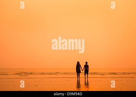 Coucher de silhouettes de couple d'amoureux sur la plage Banque D'Images