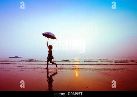 Silhouette de bonne course femme avec parapluie Banque D'Images