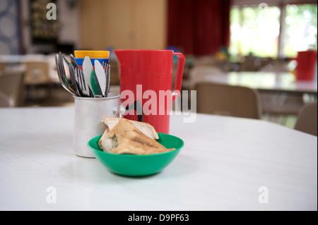 Cantine scolaire primaire UK avec des couverts, une cruche d'eau rouge et un bol de pain sur une table prête pour Banque D'Images