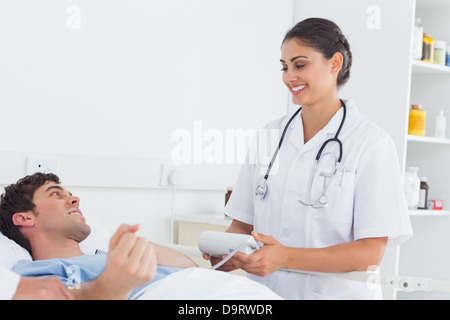 La mesure de l'infirmière attrayant la pression artérielle d'un patient Banque D'Images