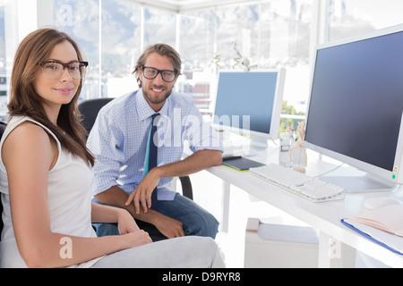 Designers assis à leur bureau et souriant Banque D'Images