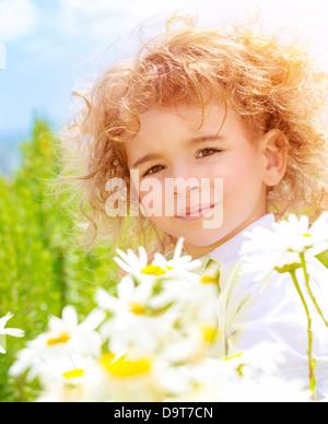 Closeup portrait of cute baby boy avec de beaux cheveux bouclés sur la marguerite champ dans journée ensoleillée, Banque D'Images