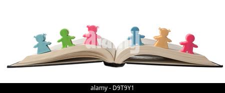 Figurines colorées sur le dessus d'un livre ouvert isolé sur fond blanc Banque D'Images