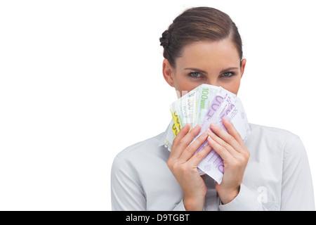 Businesswoman se cacher derrière l'argent Banque D'Images