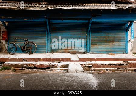 Un vélo stationné jusqu'à l'extérieur d'un atelier fermé dans la vieille ville de Fort Kochi au Kerala, en Inde. Banque D'Images