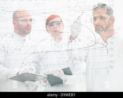 Trois scientifiques Comité de discuter d'un schéma et l'analyse des résultats d'une expérience sur une interface de verre, ils se trouvent derrière elle