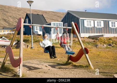 Les enfants jouent sur une balançoire à Qaanaaq, Groenland Banque D'Images