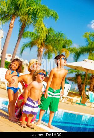 Jolie et grande famille debout près de la piscine et regarder dans le ciel, profitant des vacances, expression du visage Banque D'Images
