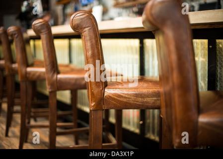 Une rangée de chaises tabouret de bar en cuir marron alignés à côté d'un bar à une taverne. Banque D'Images