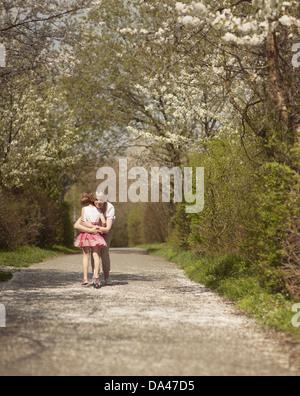 Mother hugging young girl in distance dans un parc Banque D'Images