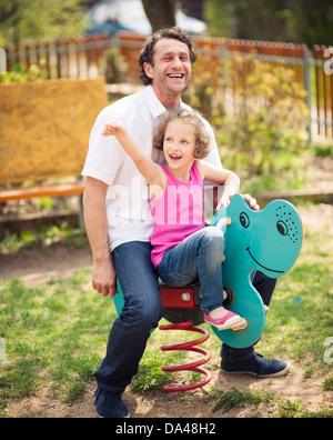 Père et fille sur l'aire de jeux sur ressort Banque D'Images