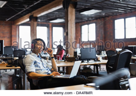 Smiling entrepreneur working on laptop in creative office space Banque D'Images