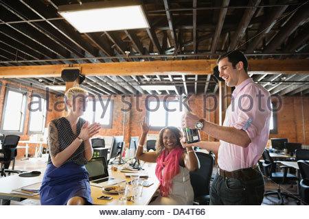 Célébrer les entrepreneurs avec champagne in office Banque D'Images