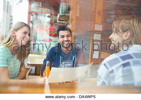 Groupe d'amis à la recherche au menu de traiteur Banque D'Images