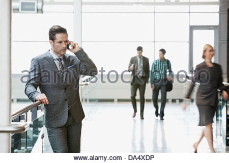Businessman using mobile phone in office building Banque D'Images