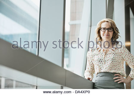 Portrait of businesswoman standing by window in office Banque D'Images