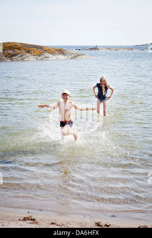 Enfants (8-9) baignade en mer Banque D'Images