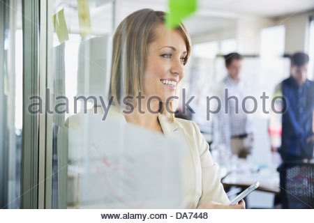 Businesswoman standing by glass wall in office Banque D'Images