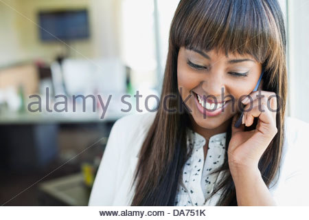 Smiling businesswoman using mobile phone in office Banque D'Images