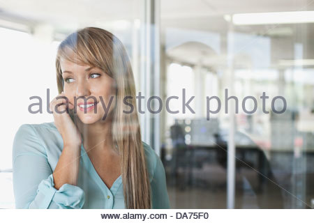 Businesswoman using mobile phone in office Banque D'Images
