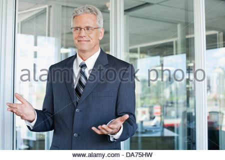 Businessman gesturing while standing in office Banque D'Images