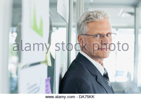 Portrait of businessman standing by glass wall in office Banque D'Images