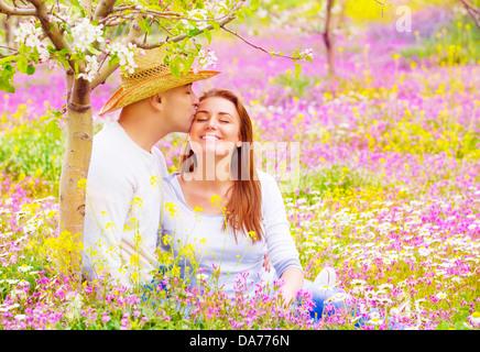 Les amateurs de plein air, les baisers heureux date romantique dans le jardin en fleurs, magnifique jeune famille, l'affection et l'amour concept
