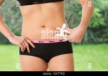 Young woman measuring son corps à l'aide de graisse à coulisse Banque D'Images