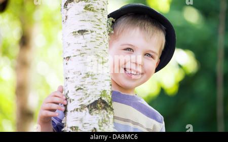 Cheerfu et mignon garçon se cacher lui-même dans le jardin Banque D'Images