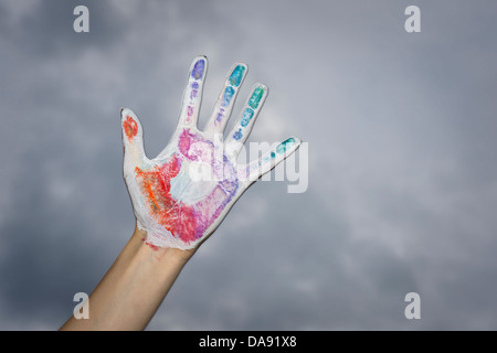 Painted Hand Against Cloudy Sky Banque D'Images