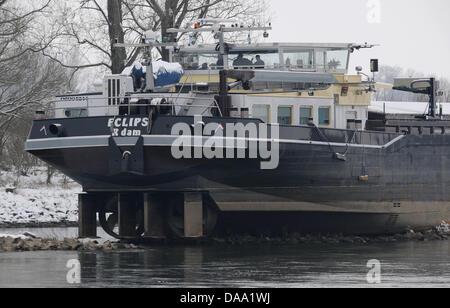 Ein Binnenfrachter steht am Samstag (05.01.2010) nahe Osterhofen (Niederbayern) Am Ufer der Donau auf einer Buhne.Der niederländische Frachter bereits im Dezember guerre auf Grund gelaufen. Nachdem das Wasser der Donau in den letzten Tagen zurückgegangen, liegt das Schiff ist völlig auf dem Trockenen. Jetzt Warten auf der Kapitän Hochwasser. Foto: Armin Weigel dpa/lby