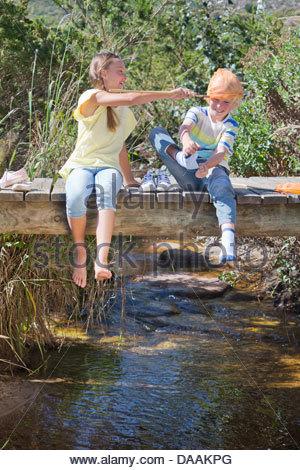 Garçon et fille jouant avec filet de pêche sur la passerelle au-dessus de stream Banque D'Images