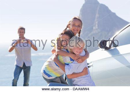 Portrait of happy family hugging extérieur près de ocean Banque D'Images