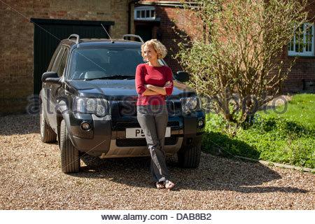 Une femme mature, debout devant une voiture à l'allée d'une maison Banque D'Images