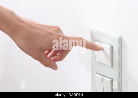 Main femme allumer la lumière avec un interrupteur mural Banque D'Images