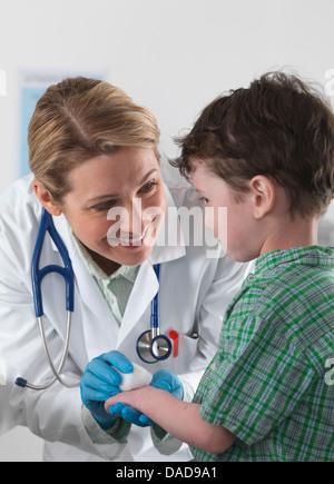 Médecin prendre soin de petit garçon avec blessure Banque D'Images