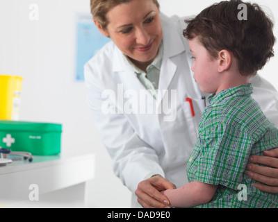Médecin prendre soin de petit garçon Banque D'Images
