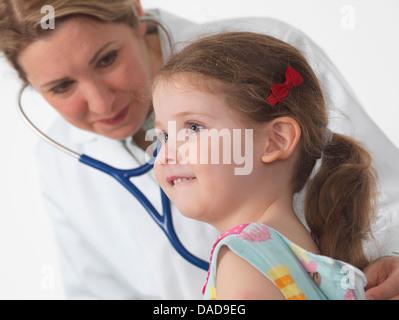 Médecin pédiatrie pour écouter le coeur et les poumons d'une petite fille en chirurgie Banque D'Images