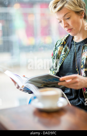 Woman Reading book in cafe Banque D'Images