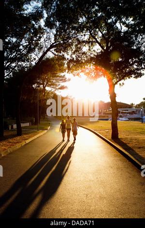 La mère et l'enfant marche sur chemin dans la lumière du soleil Banque D'Images