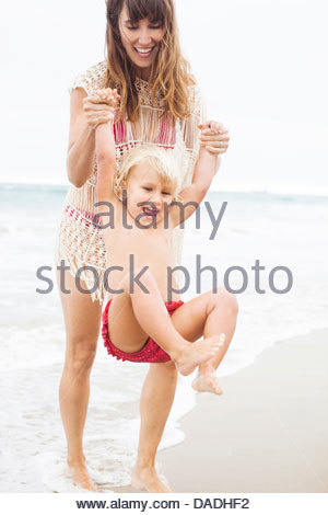 Mother swinging enfant on beach Banque D'Images