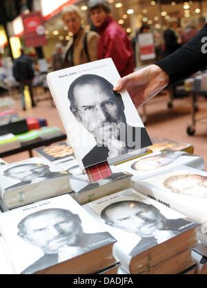 Une main tient la biographie du fondateur d'Apple, Steve Jobs, à la librairie Dussmann à Berlin, Allemagne, 27 octobre Banque D'Images