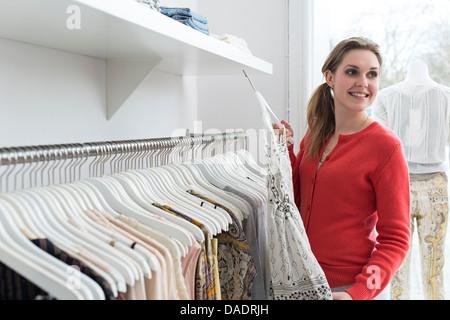 Young woman choosing dress dans mode shop Banque D'Images