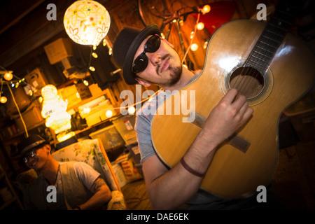 Homme portant un chapeau et des lunettes à jouer de la guitare Banque D'Images